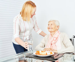 young lady serving a meal to the old woman