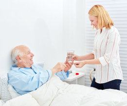 young lady giving a glass of water to the old man