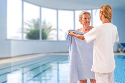 caregiver helping senior woman put on towel