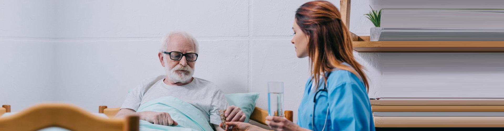 caregvier giving medicine to senior man