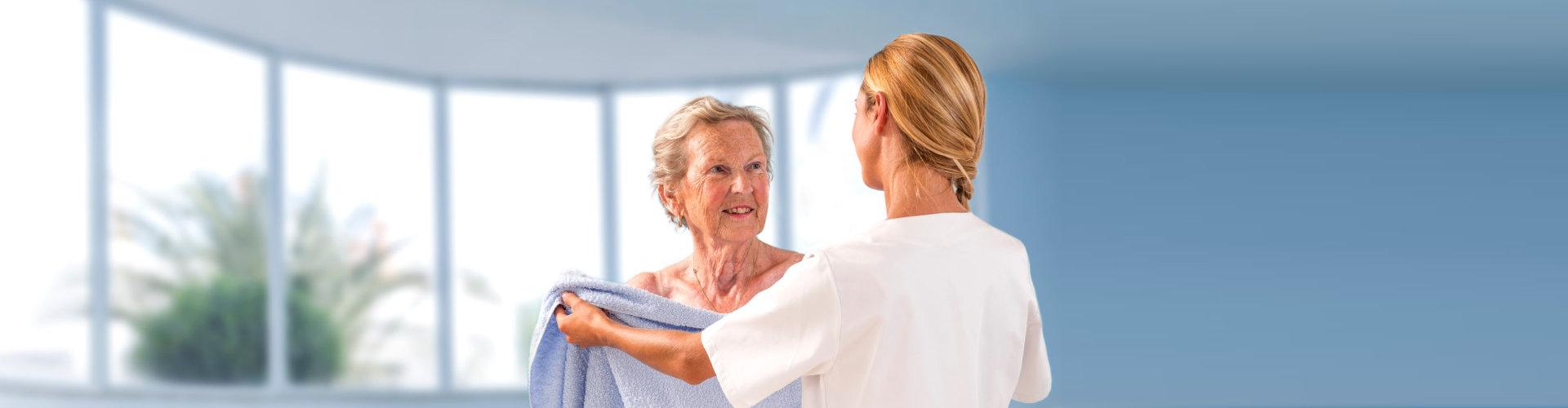 caregiver helping senior woman put on towel